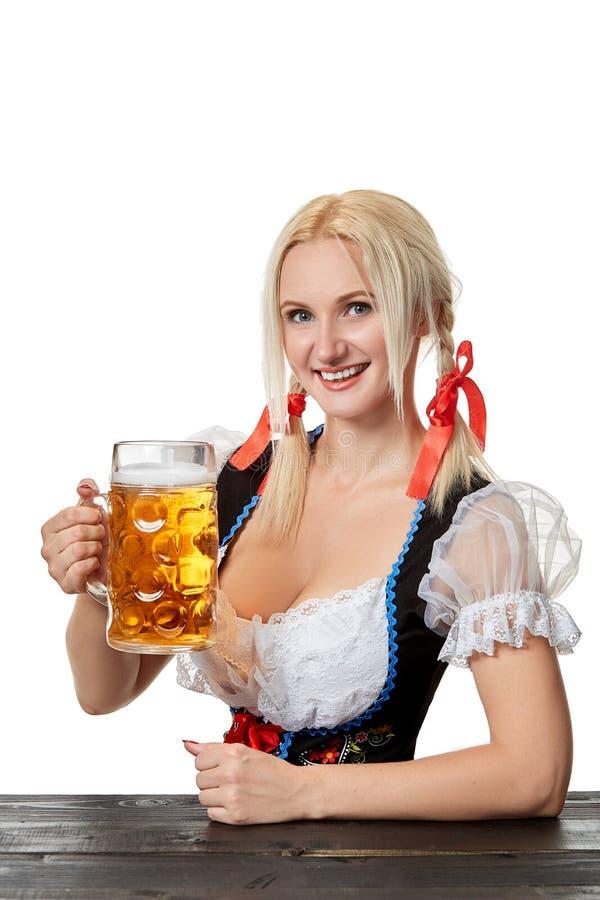 Ung bavariankvinna i dirndlsammanträde på tabellen med öl på vit bakgrund arkivbild