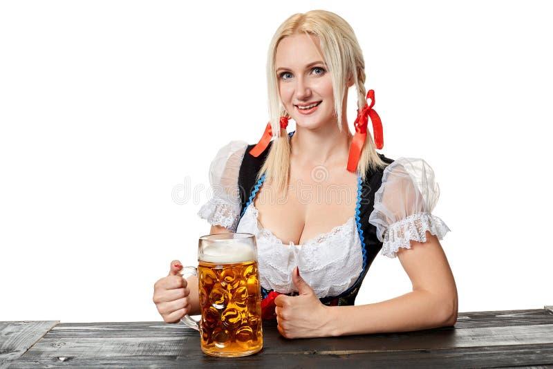 Ung bavariankvinna i dirndlsammanträde på tabellen med öl på vit bakgrund arkivfoto
