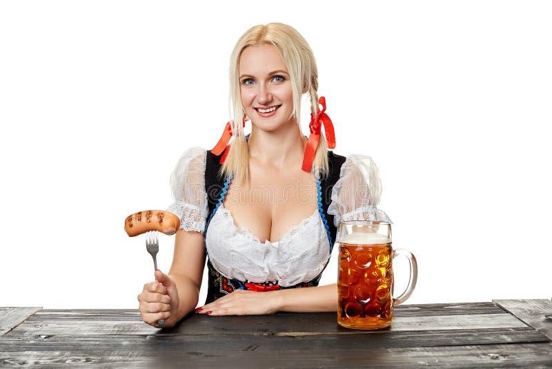 Ung bavariankvinna i dirndlsammanträde på tabellen med öl på vit bakgrund royaltyfri foto