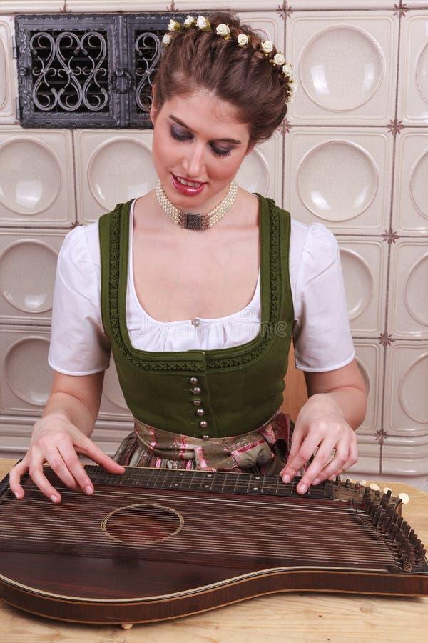 Ung bayersk flicka för lek i cittra fotografering för bildbyråer