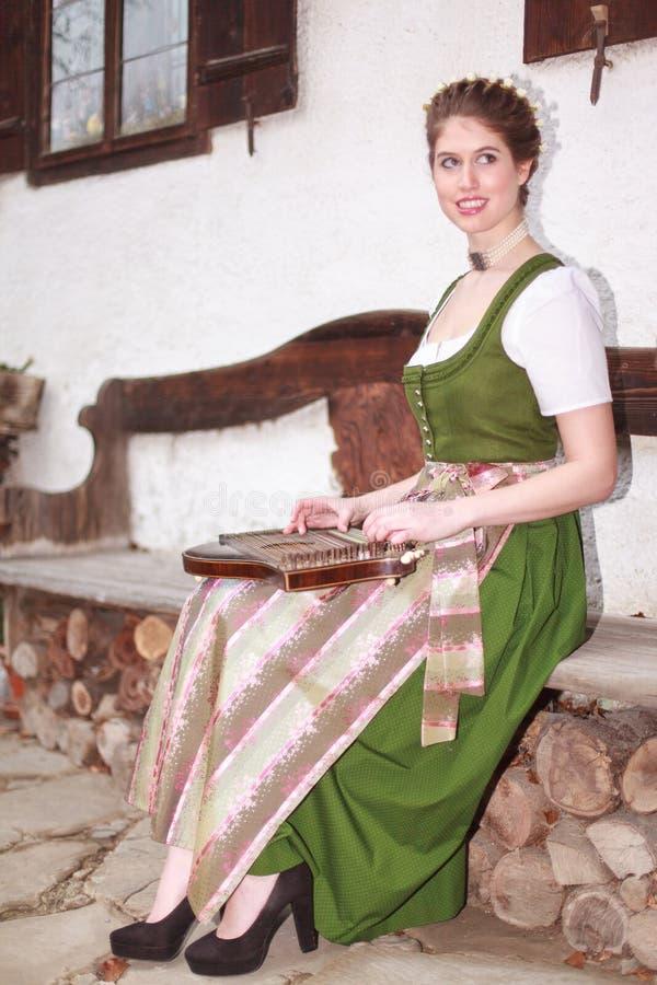 Ung bayersk flicka som spelar cittra på en bank fotografering för bildbyråer