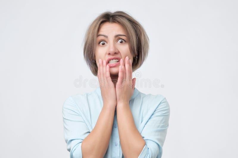 Ung bekymrad kvinna i det desperata läget som rymmer händer på huvudet fotografering för bildbyråer