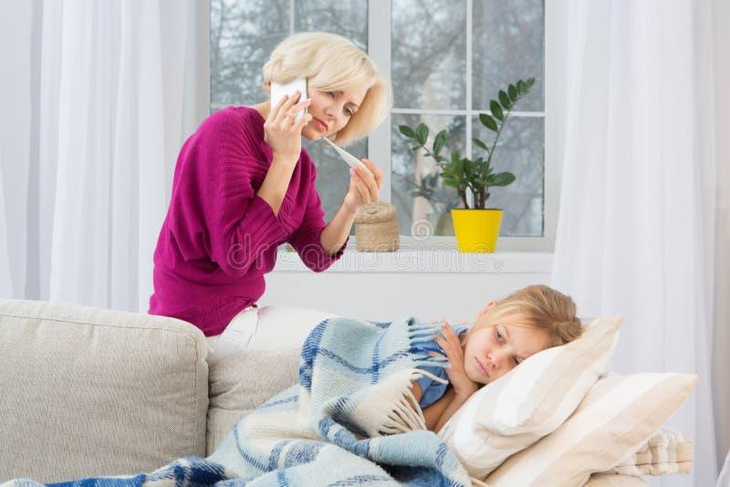 Ung bekymrad mamma som kallar doktorn som mäter temperatur av hennes dotter royaltyfri bild