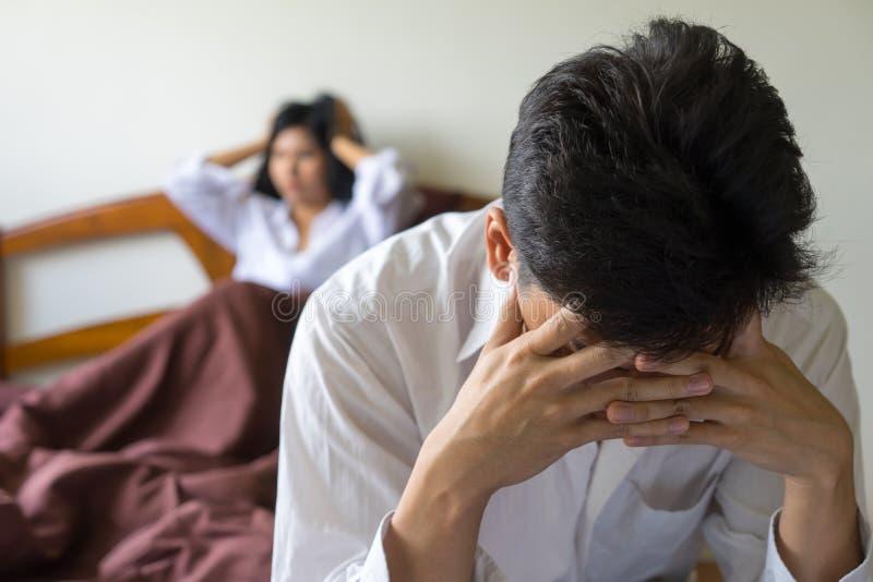 Ung bekymrad man på säng Olyckliga par som har problem i bedro arkivfoto