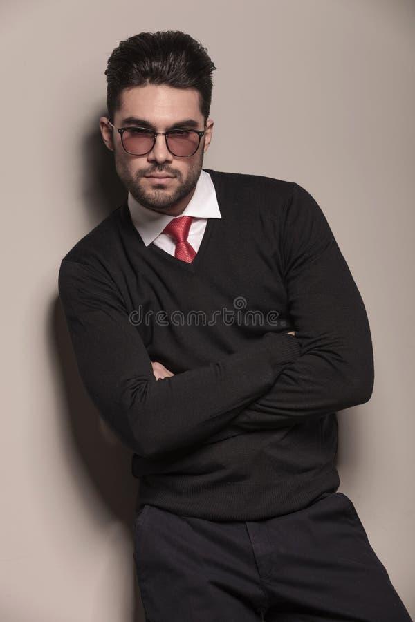Ung benägenhet för affärsman på en grå vägg royaltyfri bild