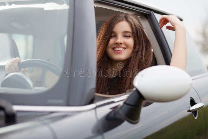 Ung beuatiful kvinna som kör en bil arkivfoto