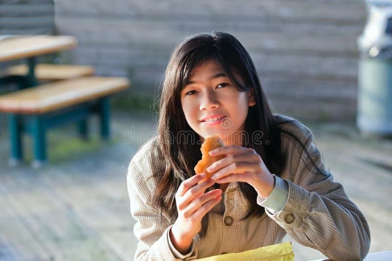 Ung biracial tonårig flicka som äter hamburgaren arkivfoto