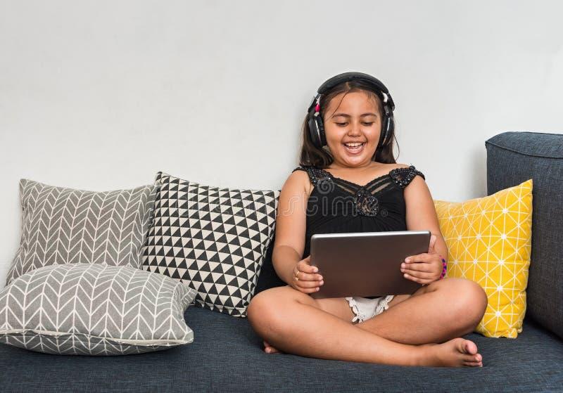 Ung blandad asian/caucasian flicka som sitter på vardagsrum genom att använda minnestavlan med hörlurar som skrattar på vilka she royaltyfri bild