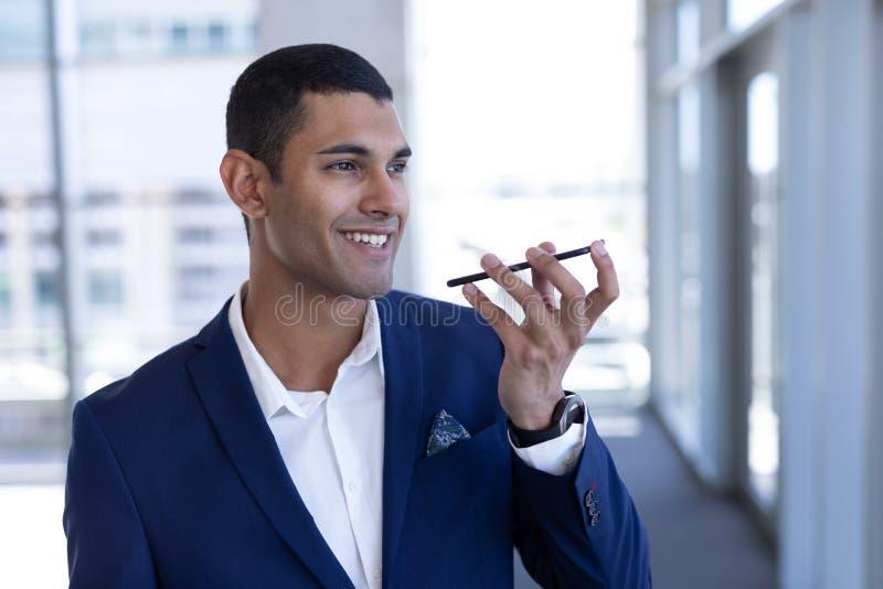 Ung blandad-lopp affärsman som talar på mobiltelefonen i modernt kontor arkivfoton