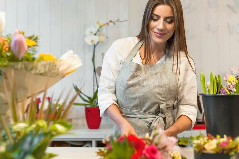 Ung blomsterhandlarekvinna i en blomsterhandel royaltyfri foto