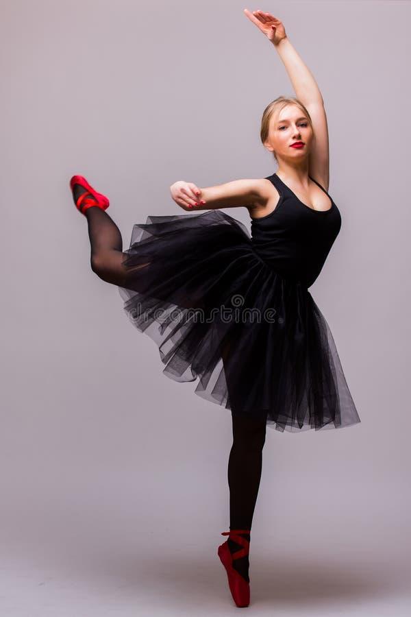 Ung blond ballerinaflickadans och posera i svarta ballerinakjol- och balettskor på grå bakgrund arkivbild