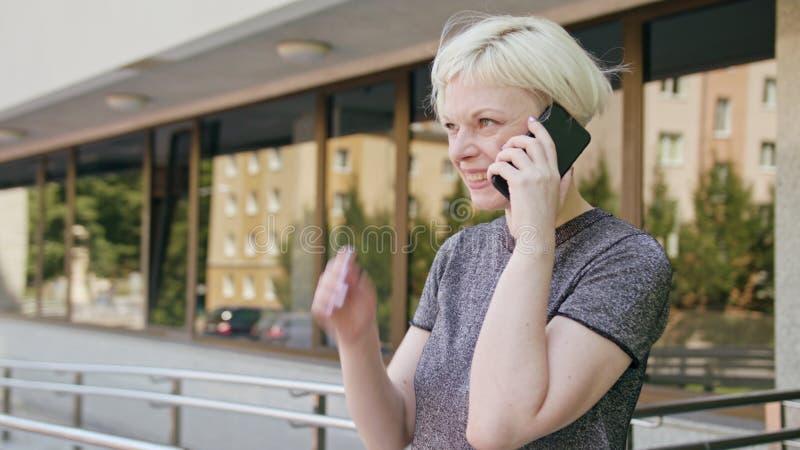 Ung blond dam Speaking på telefonen i stad arkivfoton