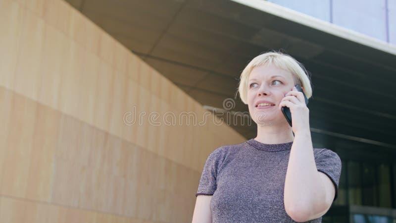 Ung blond dam Speaking på telefonen i stad royaltyfri fotografi
