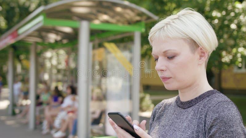 Ung blond dam Using en telefon i stad fotografering för bildbyråer
