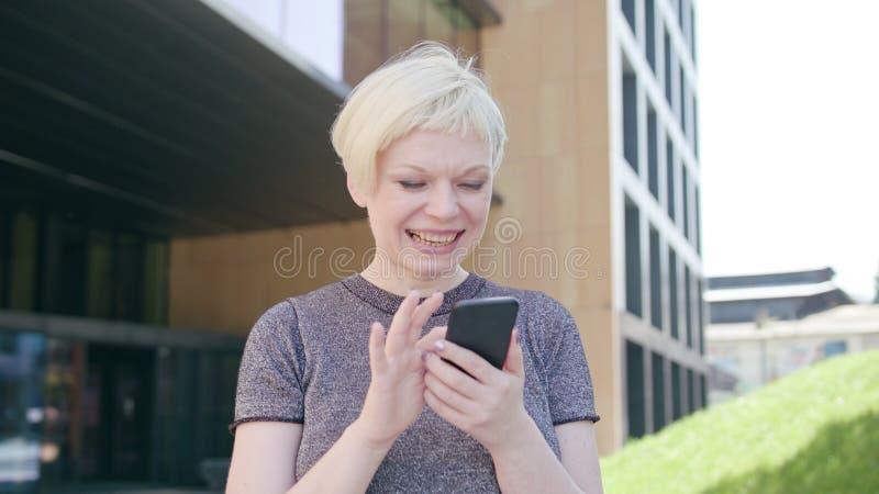 Ung blond dam Walking och använda en telefon i stad royaltyfri bild