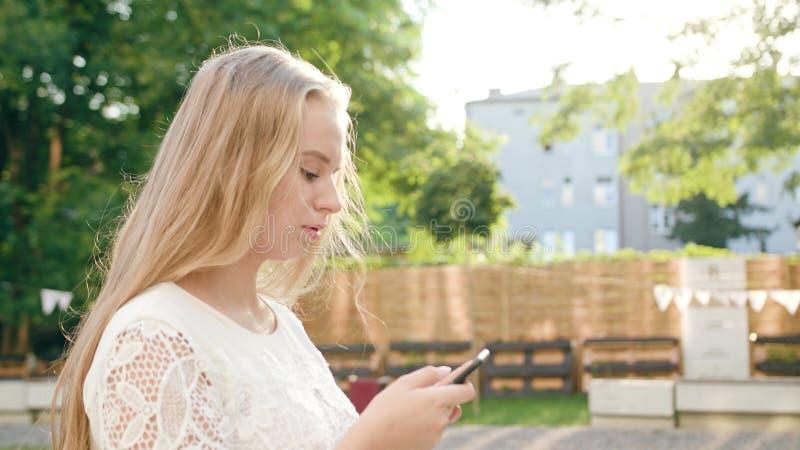 Ung blond dam Walking och använda en telefon i stad arkivbild