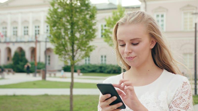 Ung blond dam Walking och använda en telefon i stad royaltyfria bilder