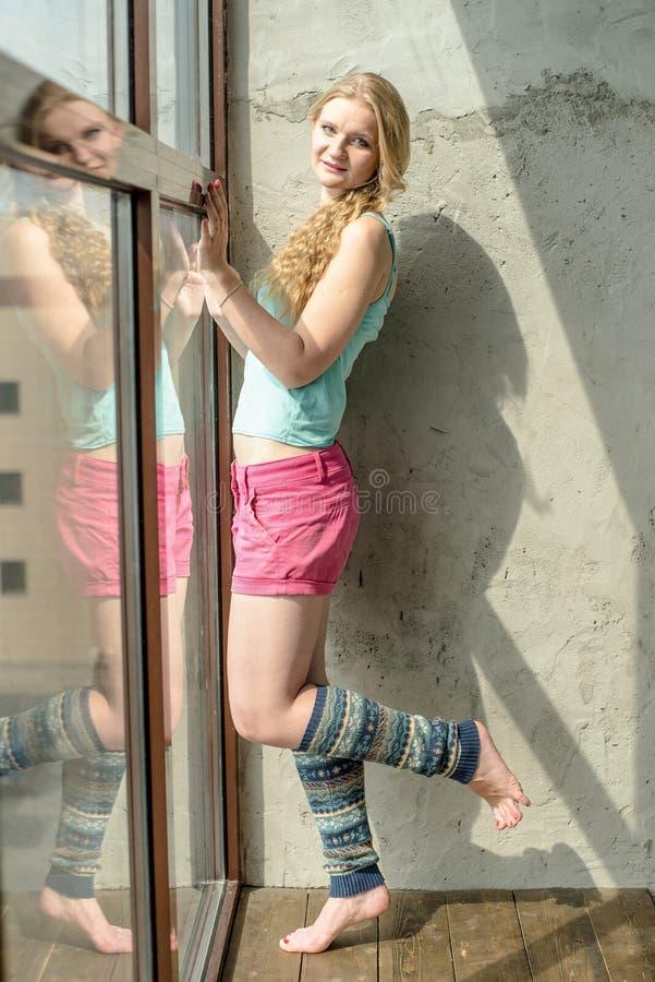 Ung blond flicka i sportärmlös tröja och kortslutningar royaltyfria bilder