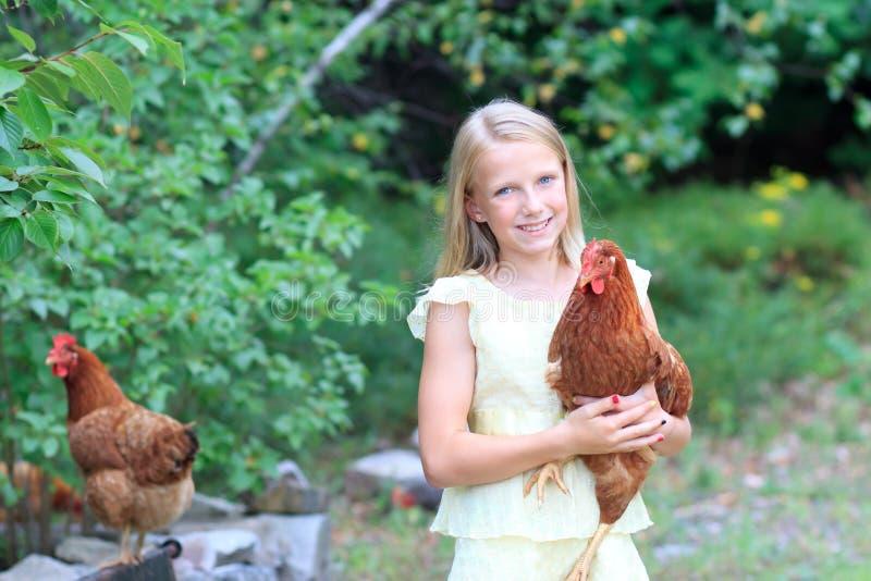 Ung blond flicka i trädgården med henne hönor arkivfoto