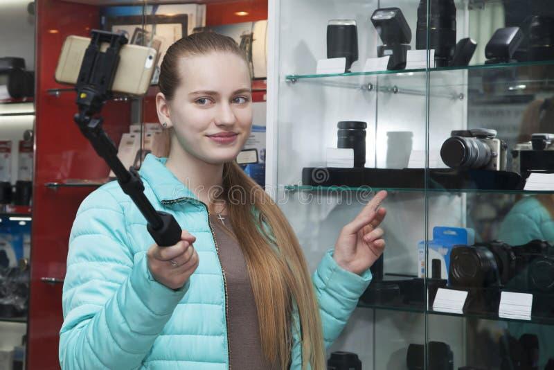 Ung blond flicka i yrkesmässiga rekord för fotoutrustninglager som är videopp till telefonen genom att använda selfiepinnen på ba royaltyfri bild