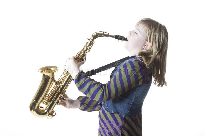 Ung blond flicka med den alt- saxofonen i studio royaltyfria bilder
