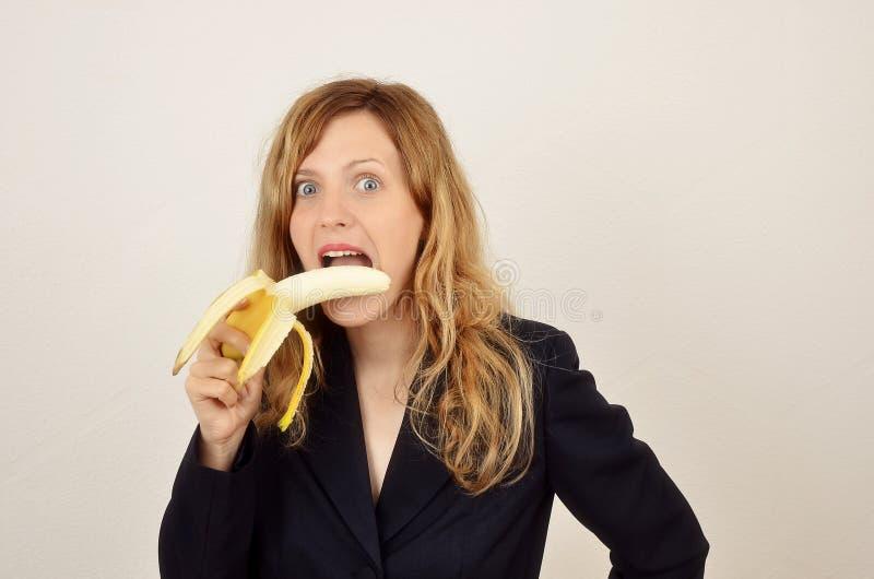 Ung blond flicka med den iklädda kontorsdräkten för banan arkivfoton