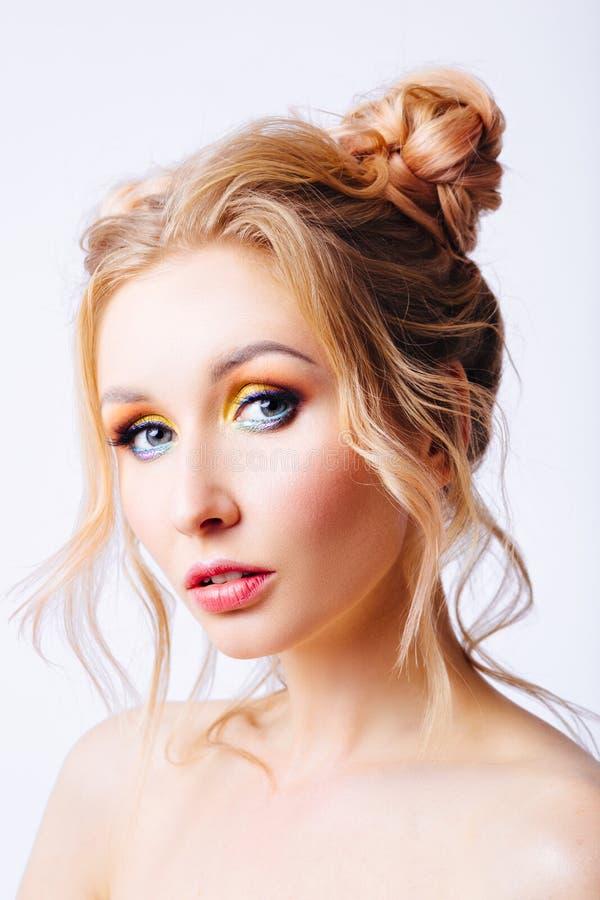 Ung blond flicka med en original- frisyr och en ljus yrkesmässig makeup arkivfoton