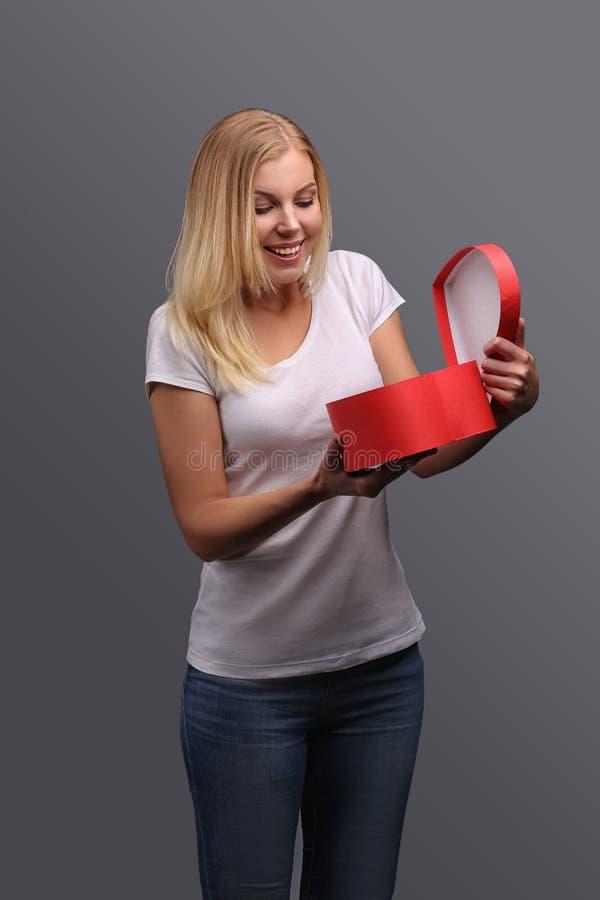 Ung blond flicka med gåvan i handen som är röd i formen av en hjärta Sinnesrörelser av glädje och överraskningen på framsidan Iso royaltyfri foto
