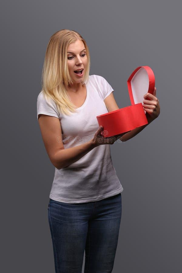 Ung blond flicka med gåvan i handen som är röd i formen av en hjärta Sinnesrörelser av glädje och överraskningen på framsidan Iso arkivfoton