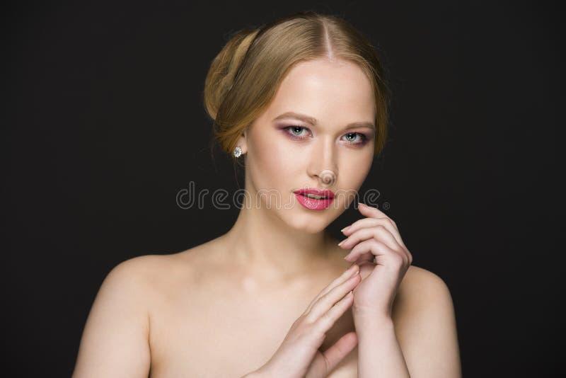 Ung blond flicka med kala skuldror som poserar på en svart, sömlös bakgrund i studio royaltyfri bild