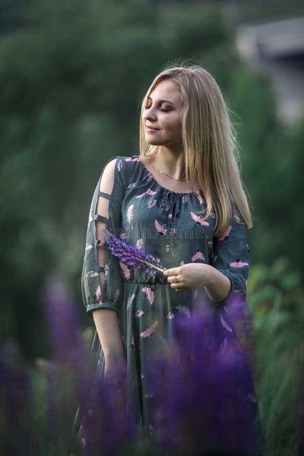 Ung blond flicka med långt hår som ligger i gräset arkivbilder