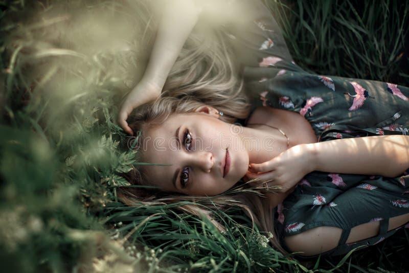 Ung blond flicka med långt hår som ligger i gräset arkivbild
