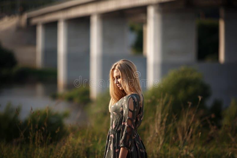 Ung blond flicka med långt hår som ligger i gräset royaltyfri fotografi