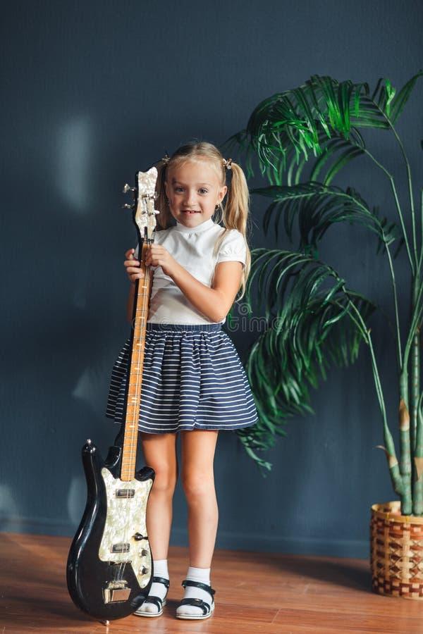 Ung blond flicka med svansar i den vita t-skjortan, kjolen och sandaler med den elektriska gitarren hemma royaltyfria bilder