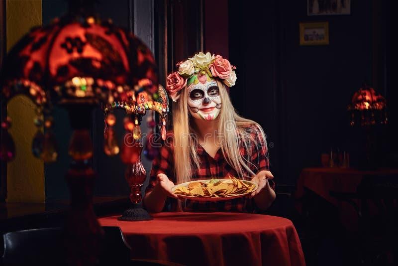 Ung blond flicka med undeadmakeup i blommakrans som äter nachos på en mexikansk restaurang royaltyfri foto