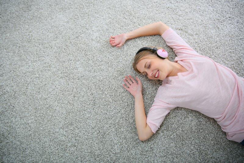 Ung blond flicka som ligger på golvet som lyssnar till musik royaltyfri foto