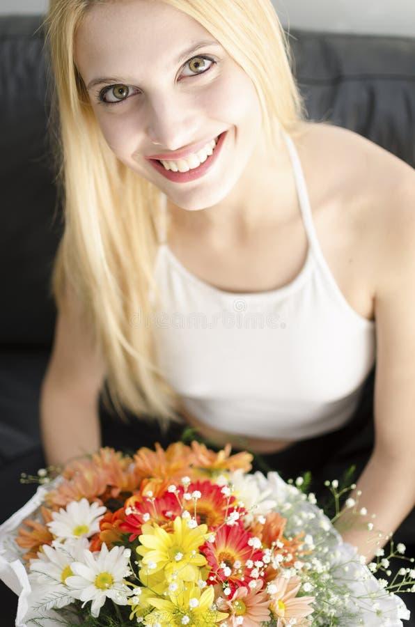 Ung blond härlig kvinna med gruppen av blommor royaltyfria bilder