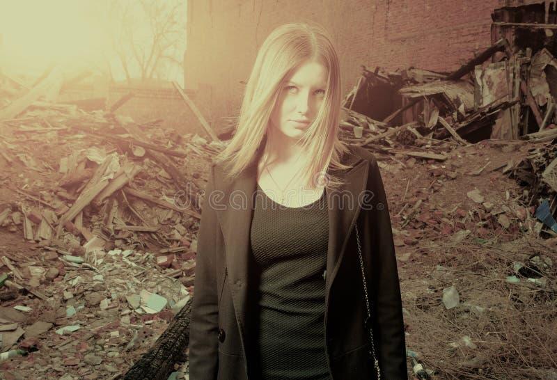 Ung blond haired flicka som bara poserar i bakbelysta slumkvarter, tonad sänka royaltyfri bild