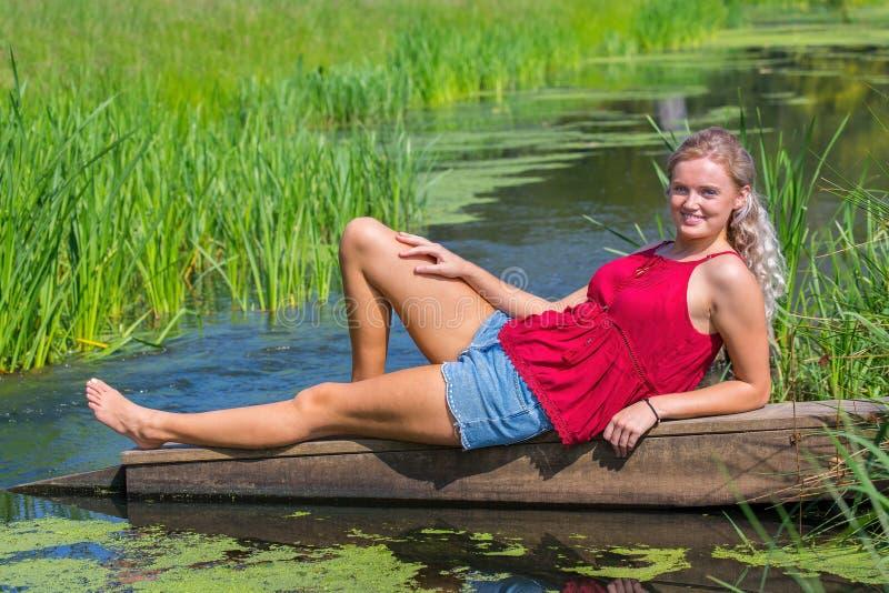 Ung blond holländsk kvinna som ligger ovanför - vatten i natur royaltyfri bild