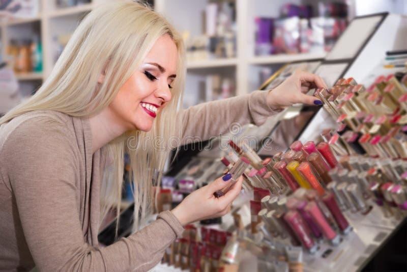 Ung blond hona som väljer lippspumlare på bildskärmen fotografering för bildbyråer