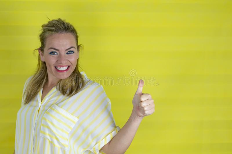 Ung blond kvinna över isolerad bakgrund som ler med den lyckliga framsidan som ser och pekar med duns upp royaltyfri fotografi