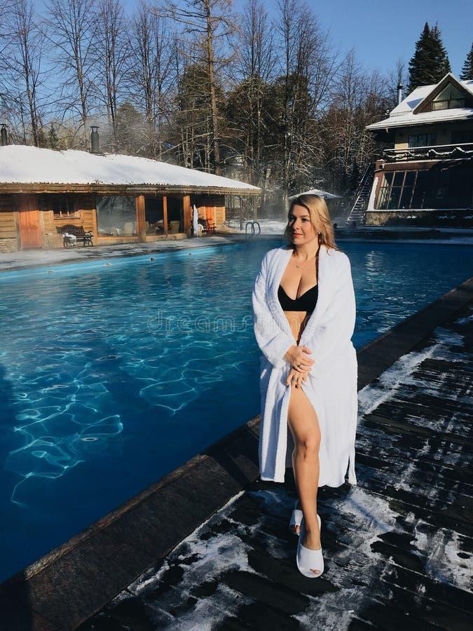 Ung blond kvinna i badrock nära utomhus- simbassäng på vinterdagen royaltyfri fotografi