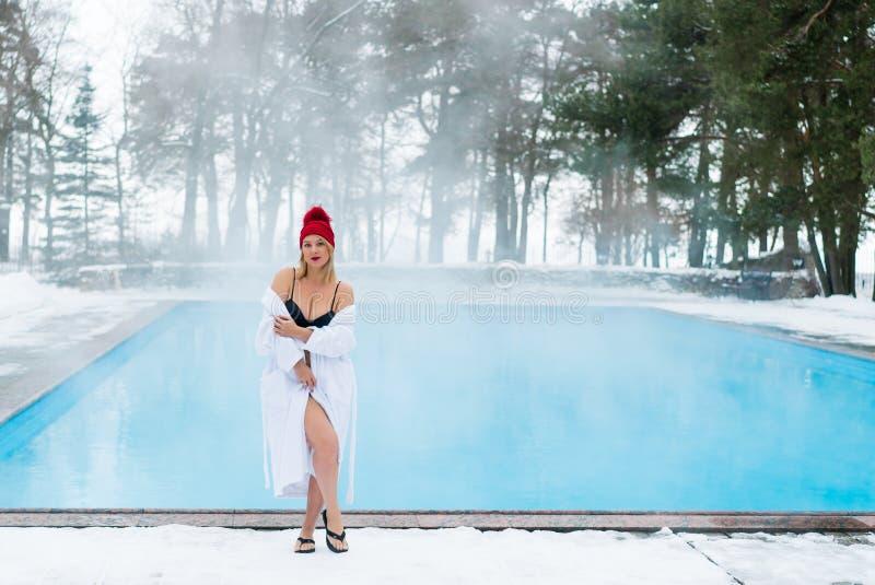 Ung blond kvinna i badrock och röd koja nära utomhus- simbassäng på vintern royaltyfria bilder