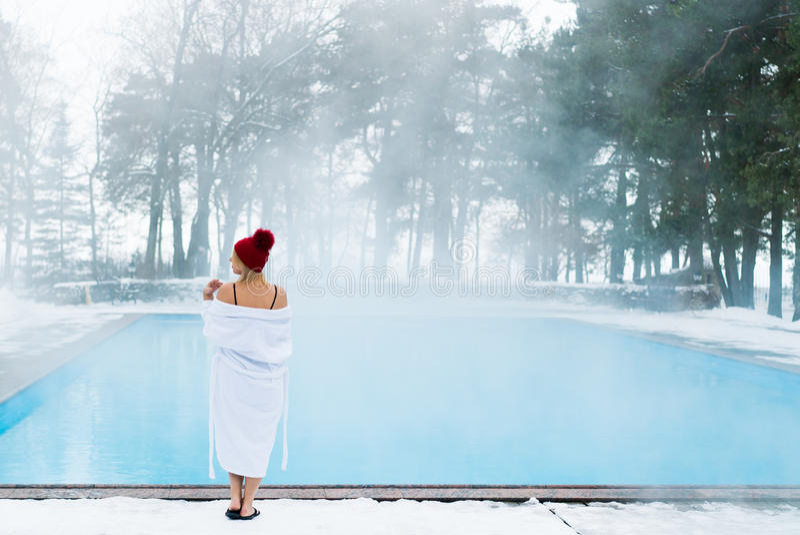 Ung blond kvinna i badrock och röd koja nära utomhus- simbassäng på vintern arkivfoto