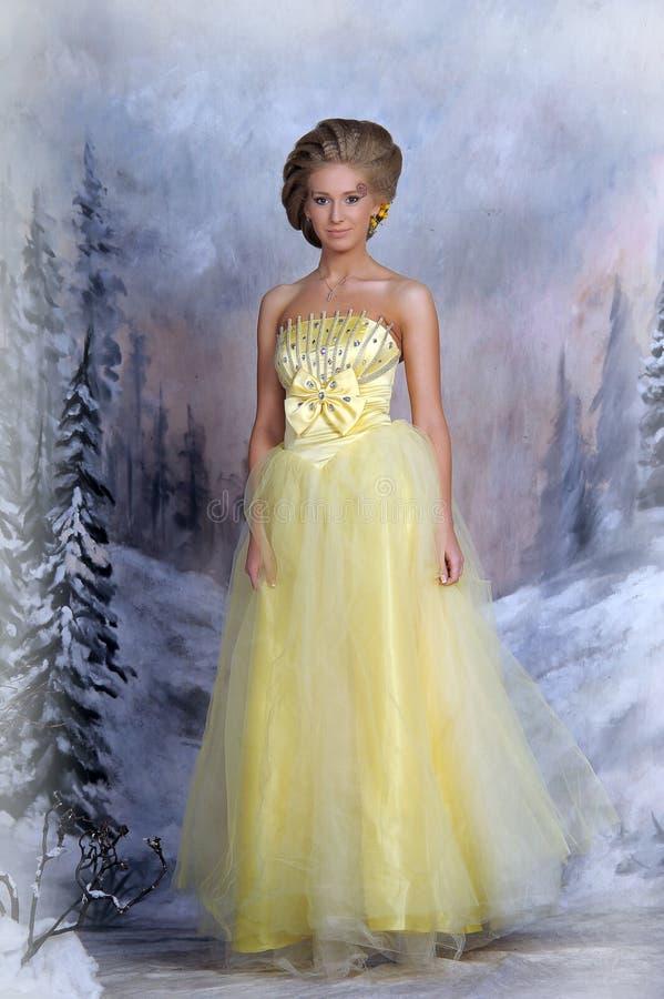 Ung blond kvinna i en elegant gul klänning arkivbild