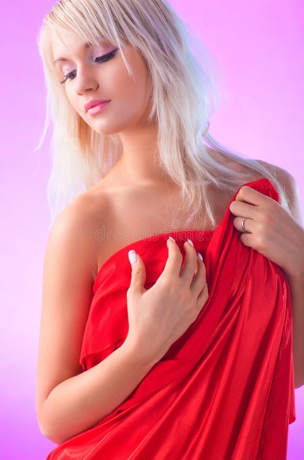 Ung blond kvinna i röd klänning arkivfoto