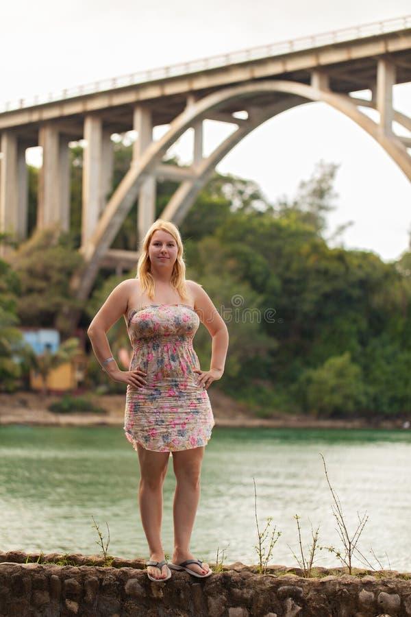 Ung blond kvinna i sommarklänning nära den höga bron över floden fotografering för bildbyråer