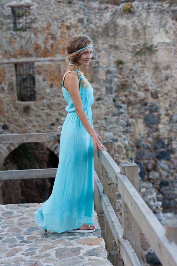Ung blond kvinna i turkosklänning med flätat hår mot royaltyfria bilder