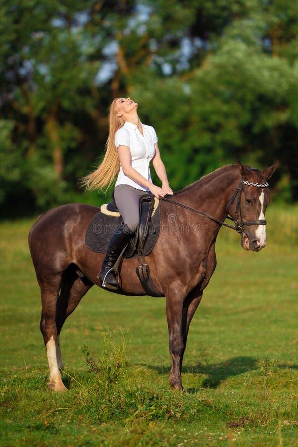 Ung blond kvinna med den långa hårjockeyryttaren som hoppar på en fjärdhäst royaltyfria bilder