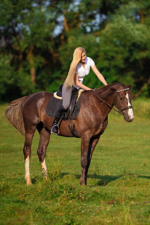 Ung blond kvinna med den långa hårjockeyryttaren som hoppar på en fjärdhäst fotografering för bildbyråer